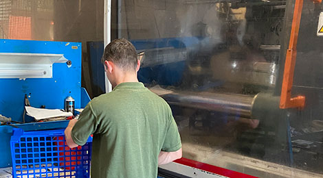 Worker using plastic injection moulding machine